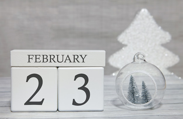 Cube shape calendar for february 23 on wooden surface and light background