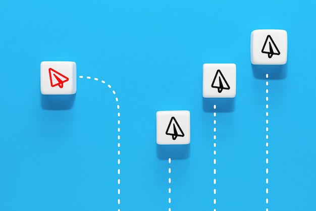 A cube with the image of a red paper airplane icon that are different from the group, blue background, business concept for new ideas creativity and innovative solution