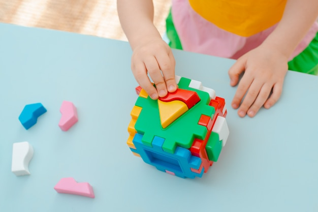 Cube with inserted geometric shapes colored plastic blocks