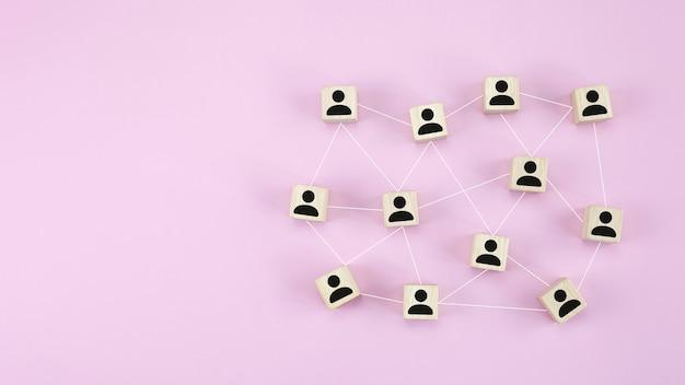 ピンクの背景に人のシンボルとグローバルネットワーク接続とキューブ