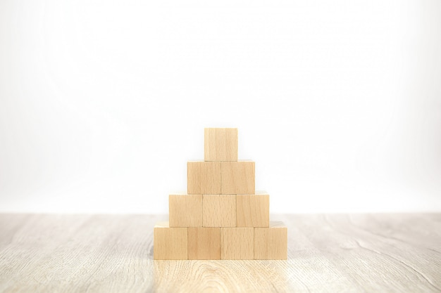 Cube wooden block toy stacked in pyramid shape without graphics.