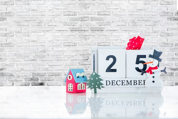 Cube wooden calendar showing date on 25 december with small wooden house, christmas tree a