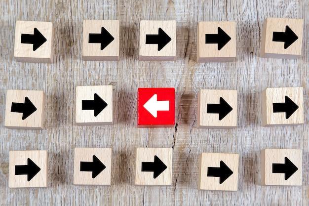 비즈니스 변화를 위해 반대 방향을 가리키는 화살표 머리 아이콘이있는 큐브 나무 장난감 블록