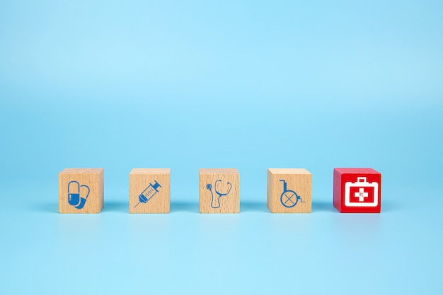 Cube wooden toy blocks with medical and first aid kid icon.