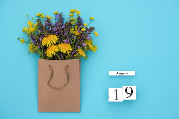 Cubes calendar august 19 and field colorful rustic flowers in craft package on blue background