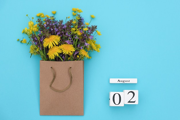 Cubes calendar august 2 and field colorful rustic flowers in craft package