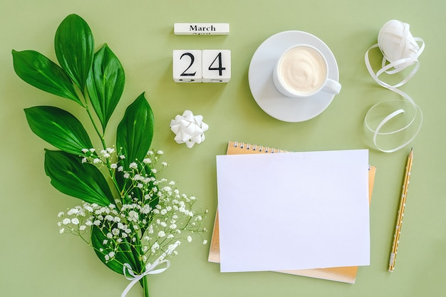 Cubes calendar march 24. notepad, cup of coffee, bouquet flowers on green background.