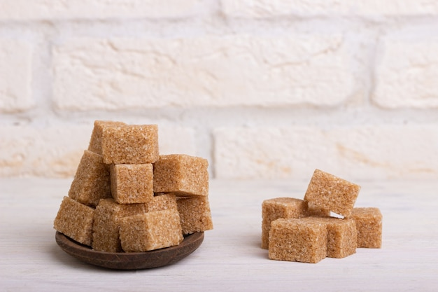Cubes of cane sugar in a wooden spoon
