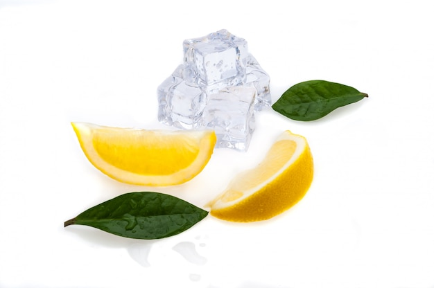 Cubes of cold ice, two slices of fresh yellow lemon and green leaves on white isolated background.