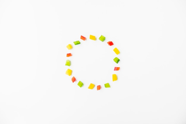 Cubes of colorful bell peppers forming frame on white background