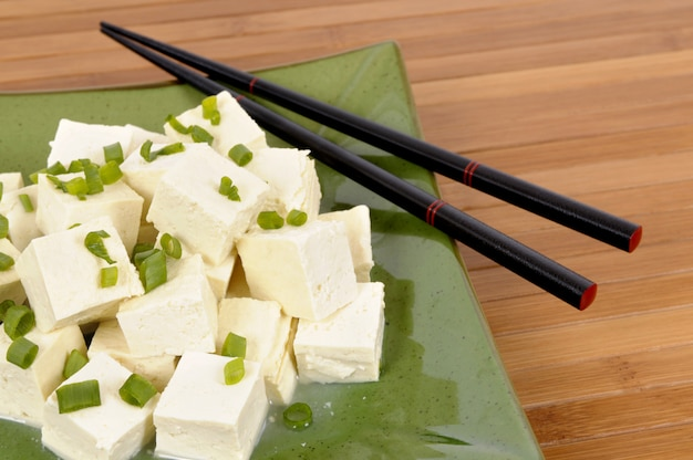Cubes of fresh tofu garnished with spring onion slices on a green plate and bamboo