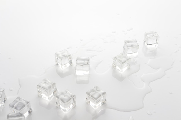 Cubes of ice and spilled water on a light background