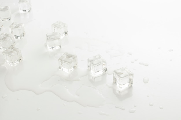 Cubes of ice and spilled water on a light