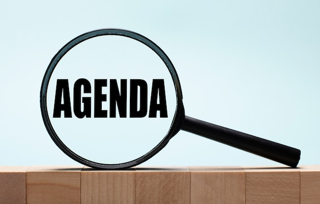 Cubes on a light blue wooden background. on them a magnifying glass with the word agenda