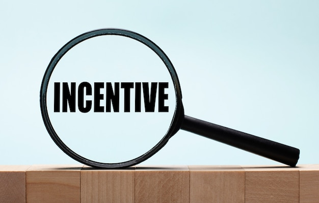 Cubes on a light blue wooden background. on them a magnifying glass with the word incentive