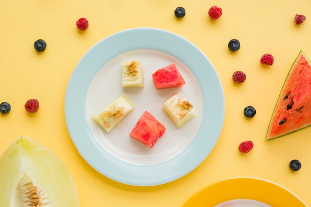 Cubes of muskmelon and watermelon on plate spread with raspberries and blueberries on yellow background