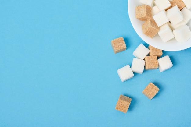Кубики коричневого и белого сахара из белой миски на синей поверхности.