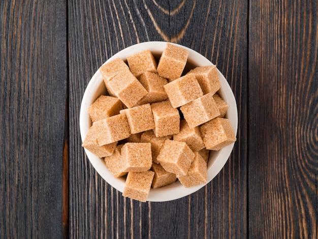 木製のテーブル、クローズアップ、側面図に白いボールで砂糖の立方体