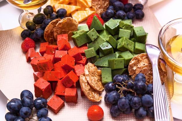 テーブルの上に果物と赤、緑のチーズの立方体