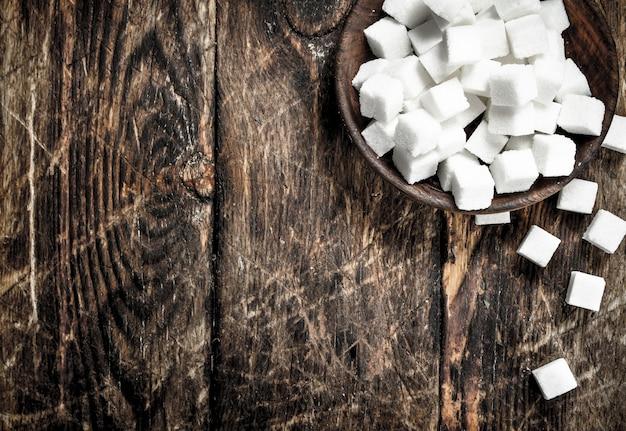 Кубики сахара в миске на деревянном фоне
