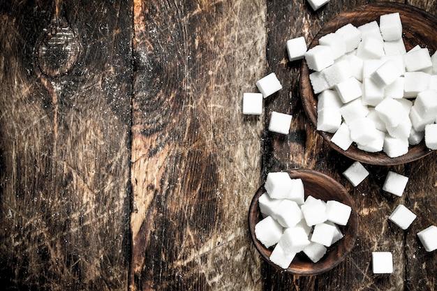 ボウルに砂糖の立方体。木製の背景に