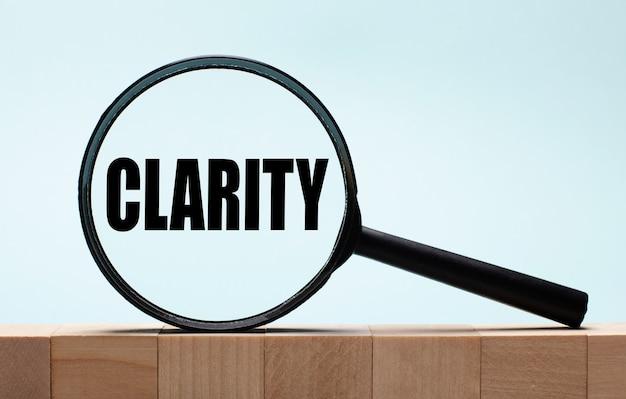水色の木製の背景の上の立方体。それらの上にclarityという言葉が付いた虫眼鏡
