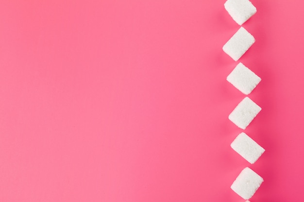 Cubes of sugar on bright pink background
