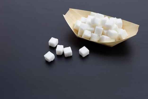 Cubes of sugar on dark surface. copy space