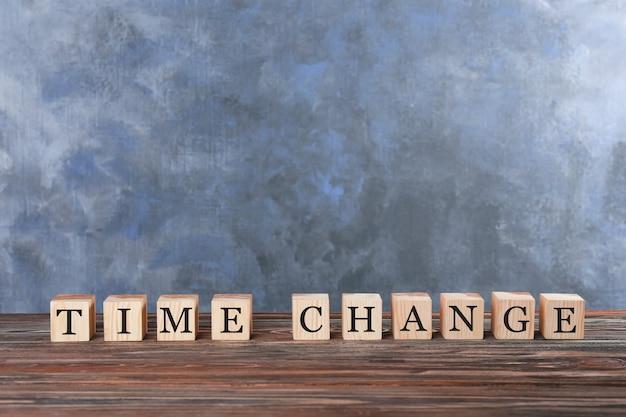Кубики с текстом изменение времени на столе против цветной стены