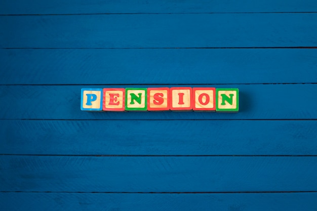 Cubes with word pension on blue wooden background.
