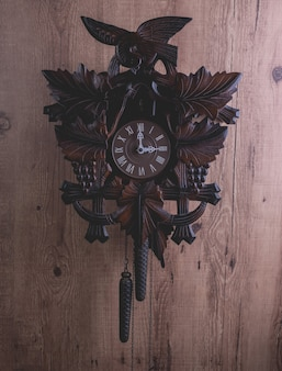 Cuckoo clock hanging on a rustic wooden wall