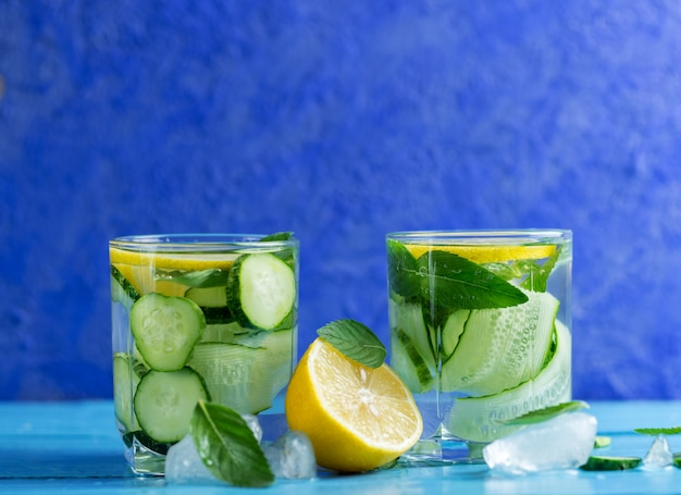 Cucumber chilled infused water with mint and lemon on blue
