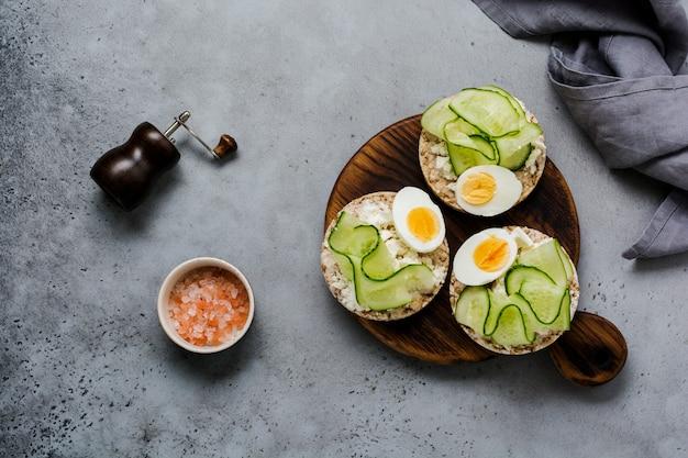 회색 콘크리트 배경에 오이, 계란, 두 부 치즈 샌드위치. 평면도.
