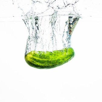 Cucumber falling in water with water splash against white background