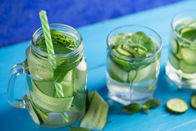 Cucumber infused water with mint on wooden blue
