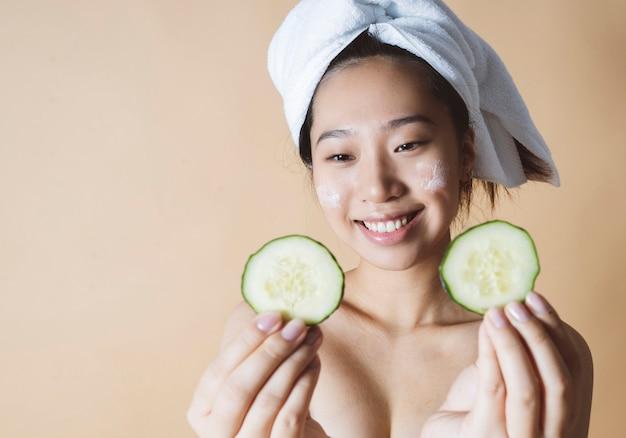 美容トリートメントをしているキュウリマスクかなりアジアの女性