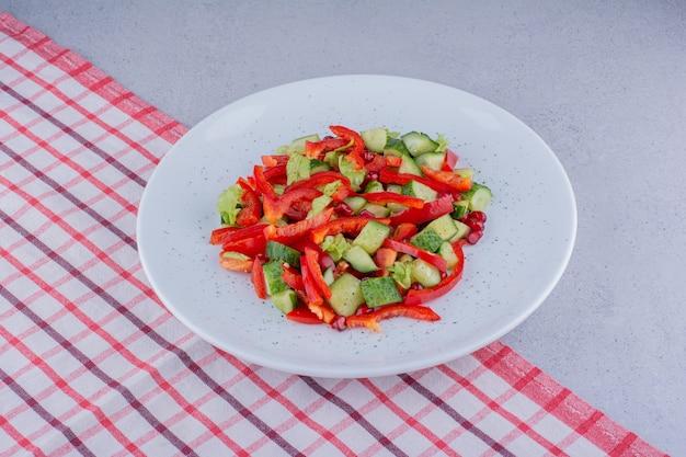 大理石の背景のテーブルクロスにキュウリ、コショウ、レタスのサラダ。高品質の写真