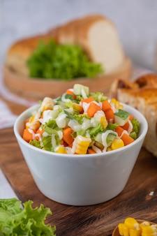 Салат из огурцов, кукуруза, морковь и салат в белой чашке.