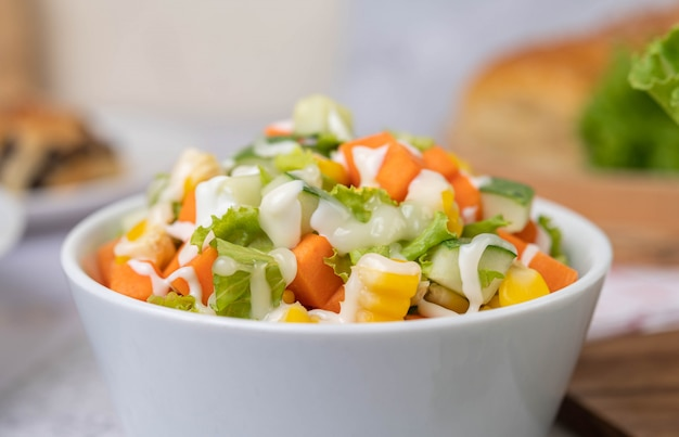 Cucumber salad, corn, carrot and lettuce in a white cup.