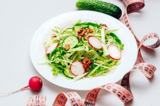 Салат из огурцов с редисом, капустой и орехами на белой тарелке и сантиметре