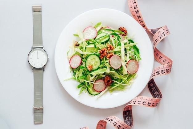 Салат из огурцов с редисом, капустой и орехами на белой тарелке
