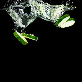 Cucumber slices falling into water splash over the black background