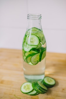 Cucumber slices in the glass water bottle on wooden desk
