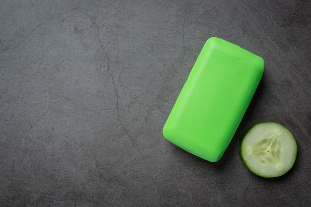 Cucumber slices and soap on dark background