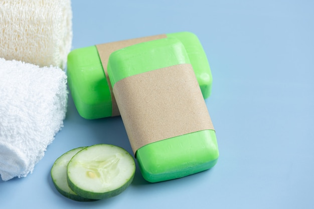 Cucumber slices and soap on light blue background