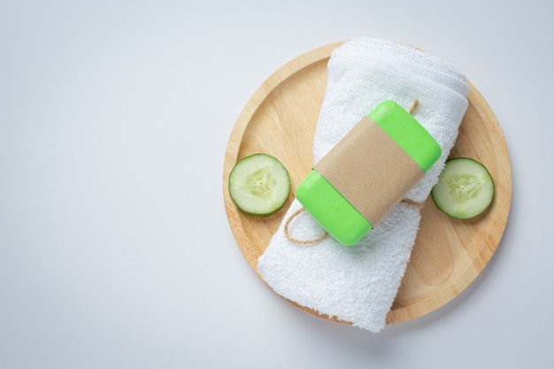 Cucumber slices and soap on white background