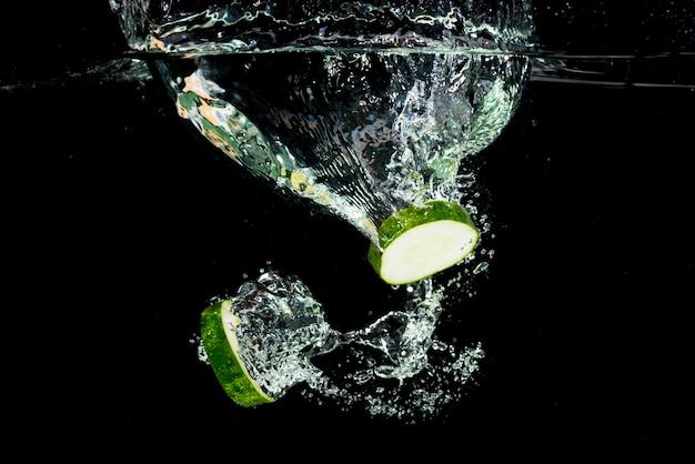 Cucumber slices splashing into water over the black background