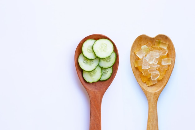 Cucumber slices with aloe vera gel in wooden spoon on white