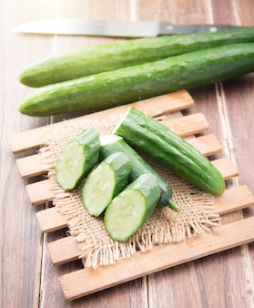 Cucumber and slices on wood background.
