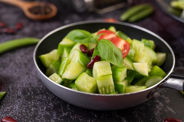 Огурец, обжаренный с помидорами и красной фасолью на сковороде.